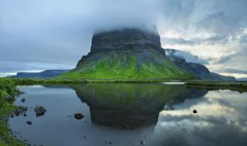 green mountain in fog with water reflection in Iceland